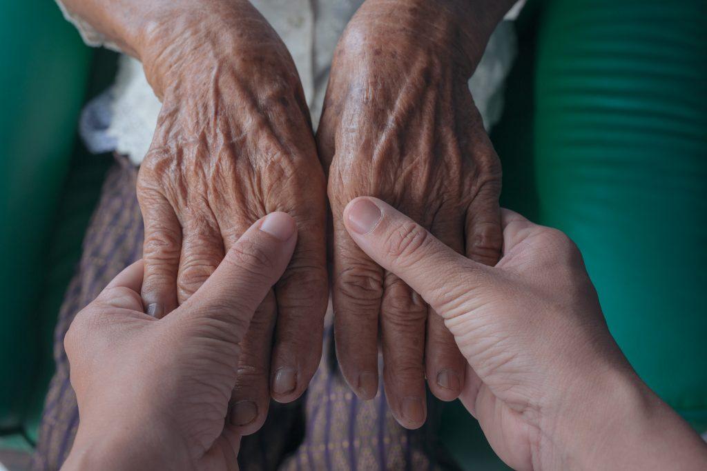 Jeune femme tenant les mains d'une personne âgées